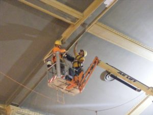 Workmen put finishing touches on ceiling of the auditorium at the new Davis Theater.